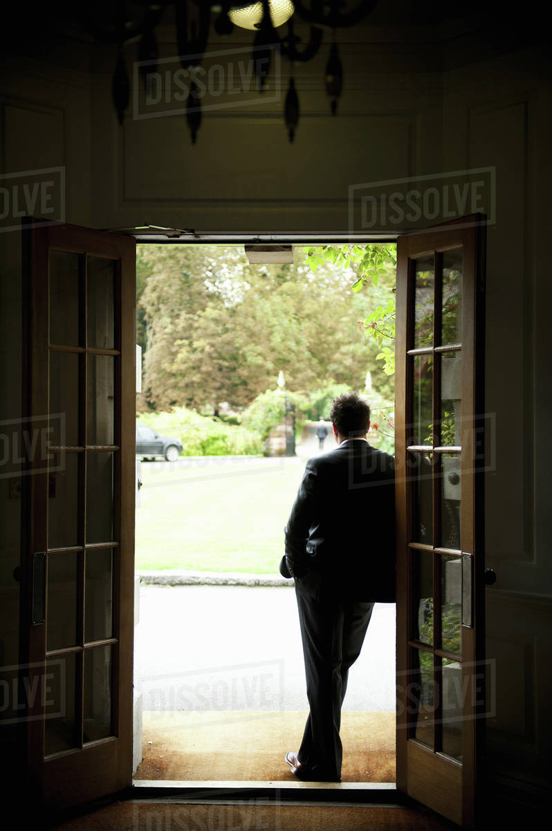 Silhouette of a man standing in a doorway leaning against the door ...