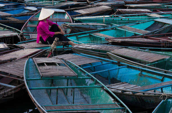 Lost in thought, a woman sits amidst a raft of boats. Ninh Binh, Vietnam Royalty-free stock photo