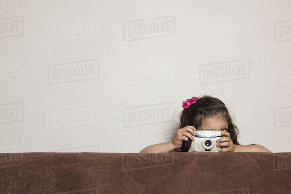 A young three year old girl crouching behind a sofa, with a toy camera, taking a picture.  Royalty-free stock photo