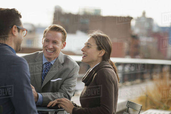 Three people standing in an open space between city buildings, talking to each other. Two men and a woman.  Royalty-free stock photo