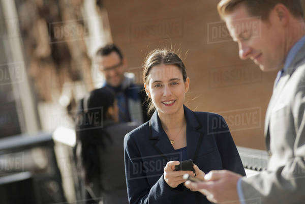 Three people standing on the sidewalk in the city, checking their phones. Two men and a woman.  Royalty-free stock photo