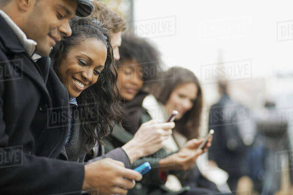 City life. A group of people on the go, keeping in contact, using mobile phones. Men and women standing in a line. Looking up and laughing. Royalty-free stock photo