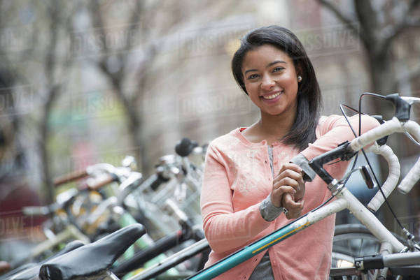 City life in spring. Young people outdoors in a city park. A young woman with black hair, wearing a peach coloured shirt, standing beside a rack of parked locked bicycles.  Royalty-free stock photo
