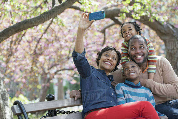 A New York city park in the spring. Cherry blossom. A woman taking a selfy picture with her smart phone of her family.  Royalty-free stock photo