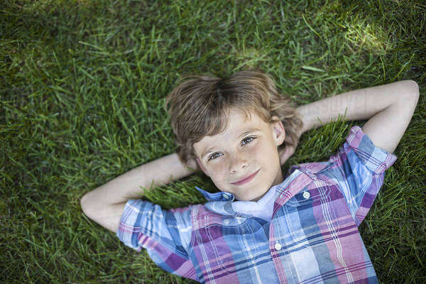 A boy lying on the grass, hands behind his head.  Royalty-free stock photo