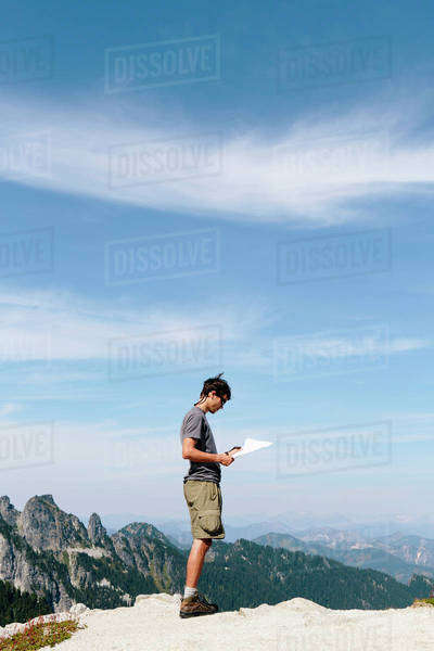 A hiker on the mountain summit, looking at a map. Surprise Mountain, Alpine Lakes Wilderness, in Mount Baker-Snoqualmie National Forest, Royalty-free stock photo