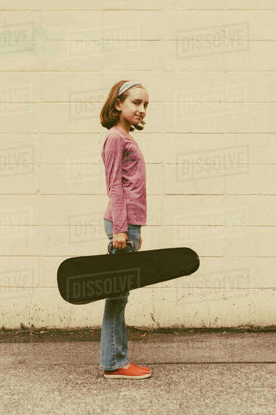 A ten year old girl carrying a violin in a case on an urban street. Royalty-free stock photo