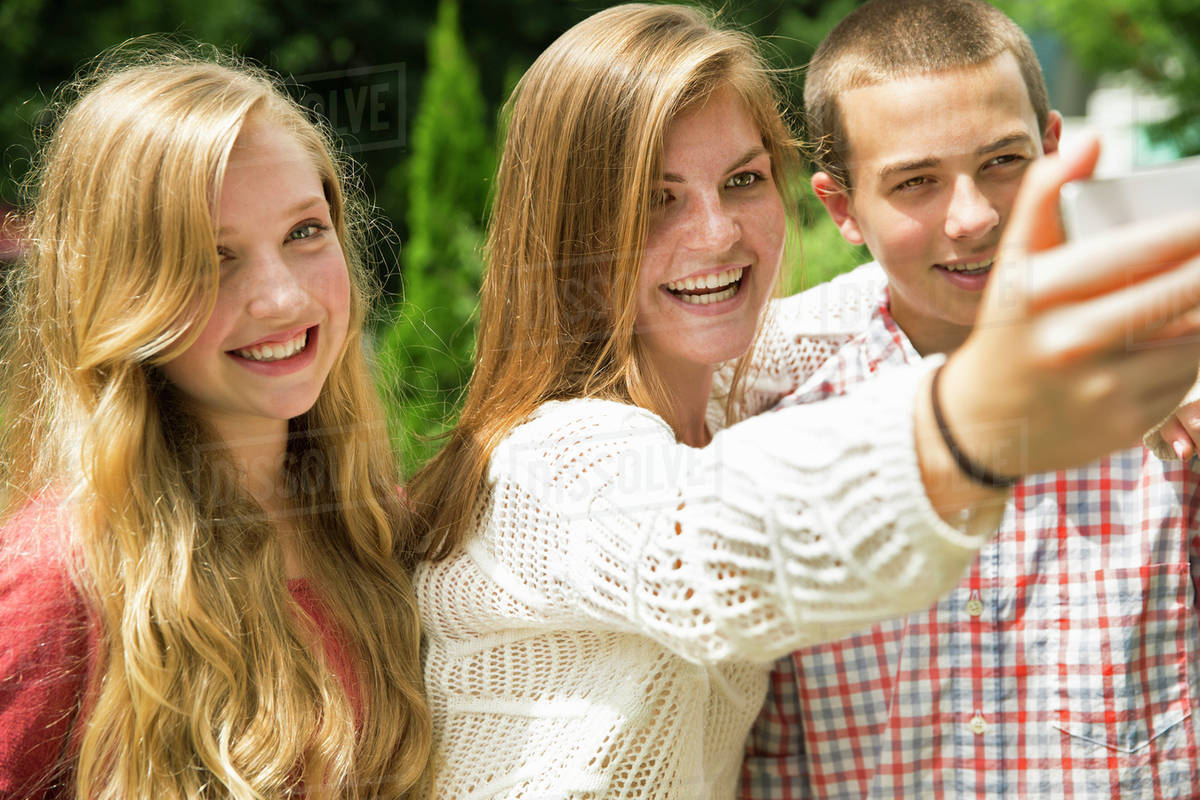 three young people two girls and a boy posing and taking selfy