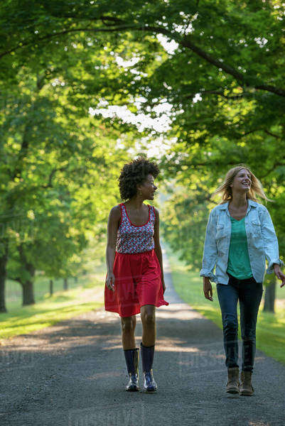 Two women walking down a path lined with trees.  Royalty-free stock photo