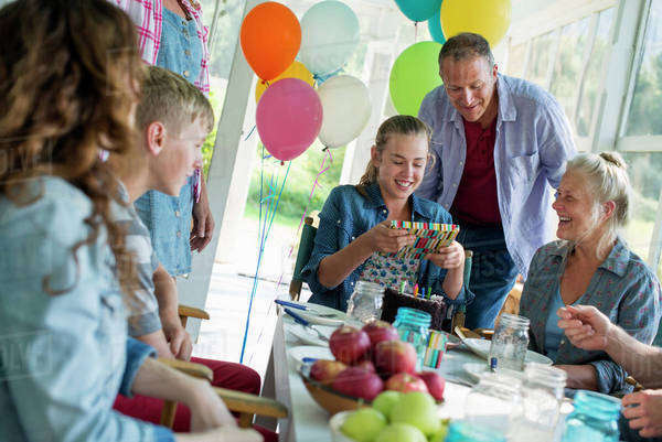 A birthday party in a farmhouse kitchen. A group of adults and children gathered around a chocolate cake. Royalty-free stock photo
