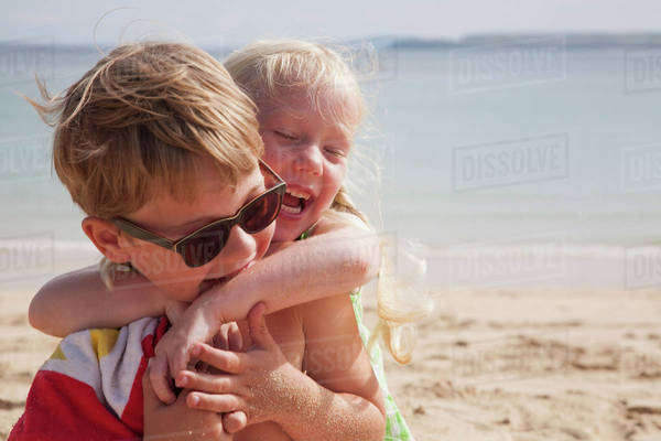 A brother and sister playfighting on the beach. A boy in sunglasses and a younger girl with her arms around his neck.  Royalty-free stock photo