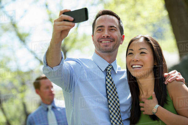 A Couple With A Smart Phone, Side By Side. A Man In The Background. Royalty-free stock photo