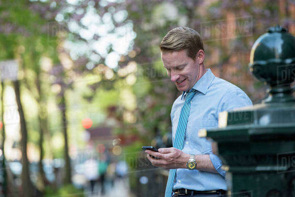 A Man In A Business Shirt And Tie, Looking Down And Checking His Phone. Royalty-free stock photo