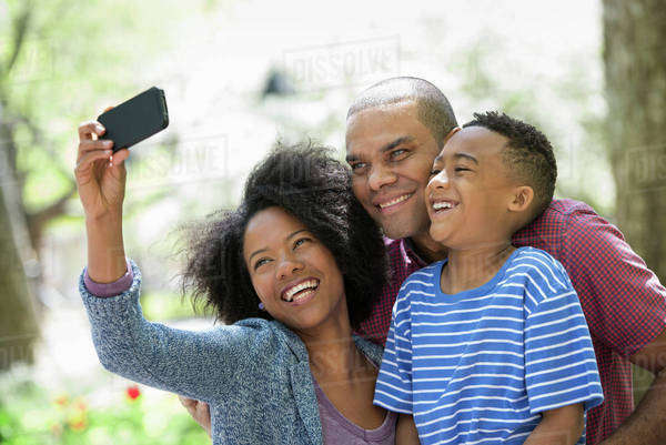 Two Adults And A Young Boy Taking Photographs With A Smart Phone.  Royalty-free stock photo