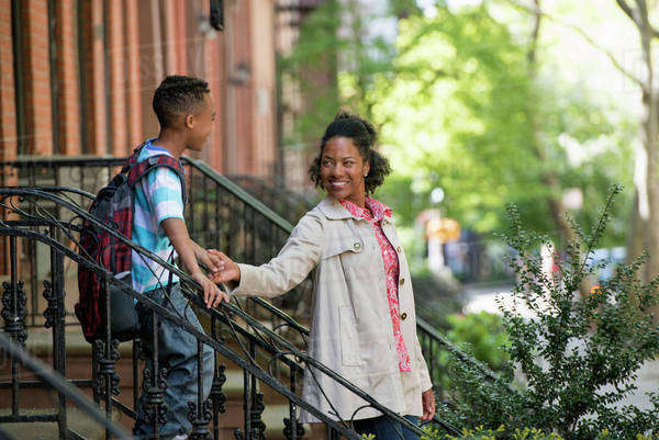 A Mother And Son, A Woman And A Boy On A Flight Of Steps Outside A Brownstone Building.  Royalty-free stock photo