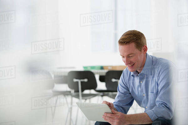 A Light Airy Office Environment. A Man Sitting Holding A Digital Tablet.  Royalty-free stock photo