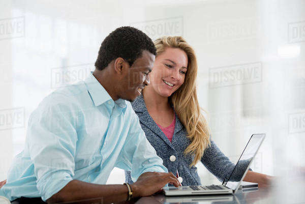 Office Interior. A Couple Seated Side By Side At A Computer. Royalty-free stock photo