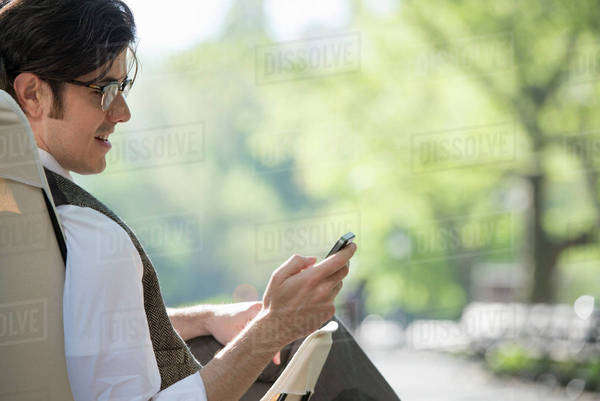 City Life. A Man Sitting In A Canvas Camping Chair In The Park Looking At His Cell Phone. Royalty-free stock photo