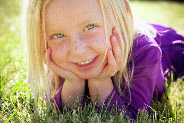 A young girl lying on the grass on her front with her chin resting on her hands. Laughing. Close up.  Royalty-free stock photo