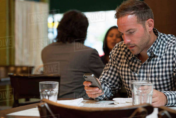 Business people out and about in the city. Two people talking to each other, and a man at a separate table checking his phone.  Royalty-free stock photo