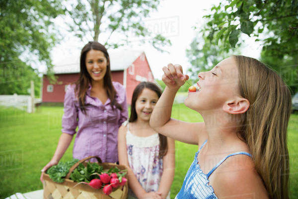 A summer family gathering at a farm. Two young girls standing by a table, one eating a fresh ripe cherry. A young woman carrying a bowl of salad. Royalty-free stock photo