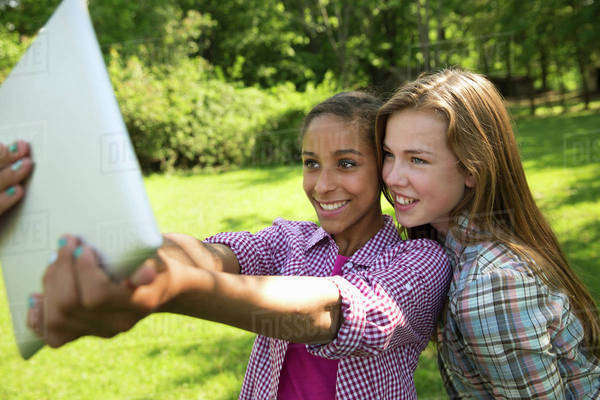 Two girls sitting outdoors on a bench, using a digital tablet.  Holding it out at arm's length. Royalty-free stock photo