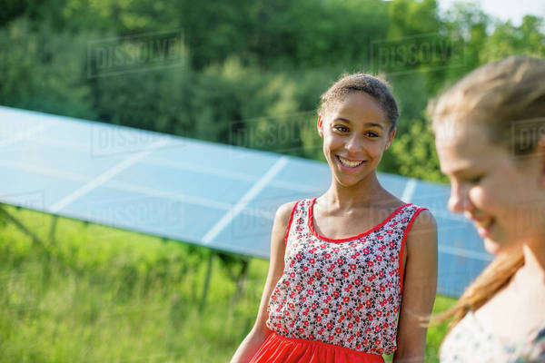 Two young girls on the farm, outdoors. A large solar panel in the field behind them. Royalty-free stock photo
