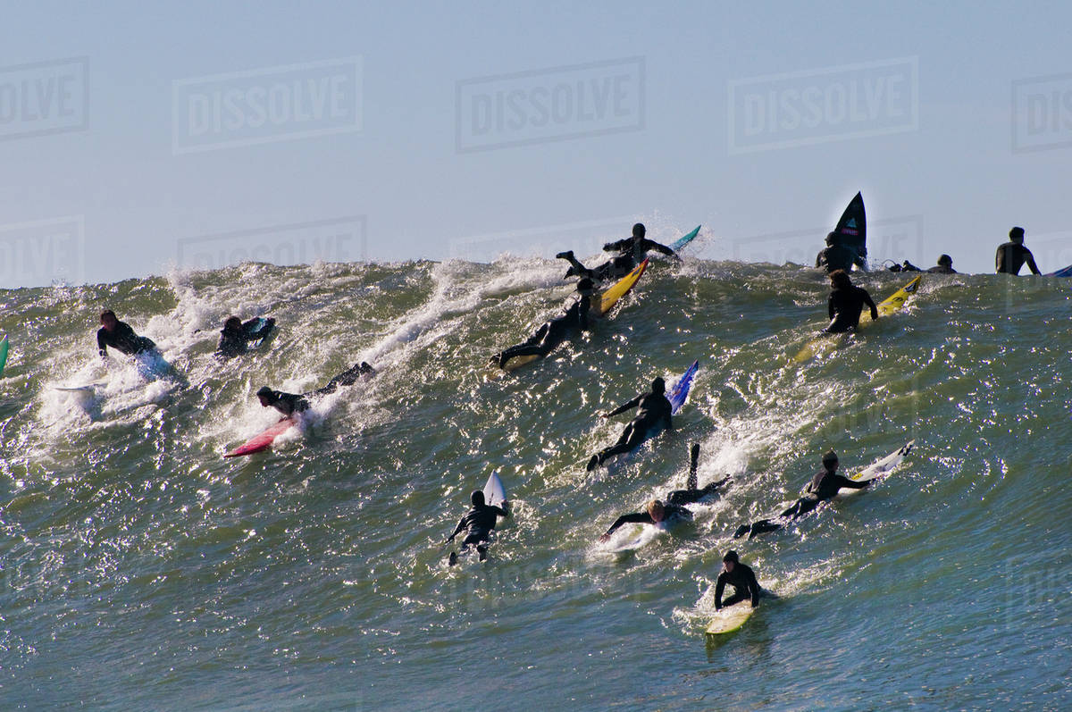 Surfers riding wave, Mavericks, Monterey Bay, California stock photo