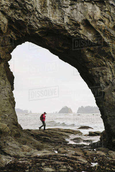 Man hiking on the beach at Hole-in-the-Rock on Rialto Beach Royalty-free stock photo