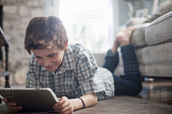 A boy lying on his front on the floor, looking at a digital tablet.  Royalty-free stock photo