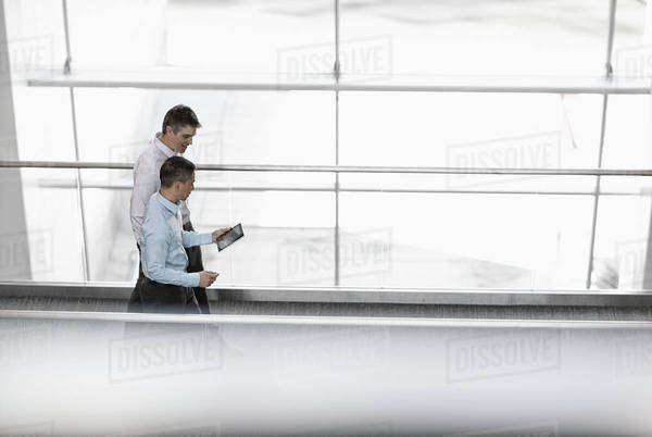 Two men standing by the large windows of a building, looking at the screen of a digital tablet. Royalty-free stock photo