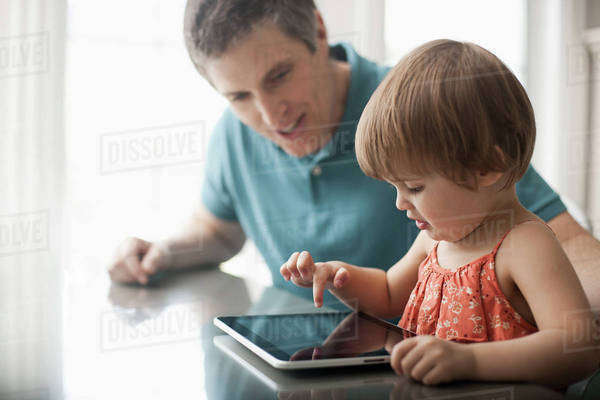 A man and a young child sitting looking at a digital tablet and touching the screen.  Royalty-free stock photo