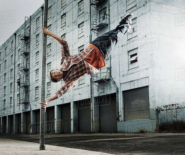 A young man breakdancing, leaping in the air, and stretching out.  Royalty-free stock photo