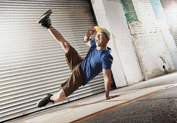 A young man breakdancing on the street of a city, balancing on one hand with his legs apart.  Royalty-free stock photo