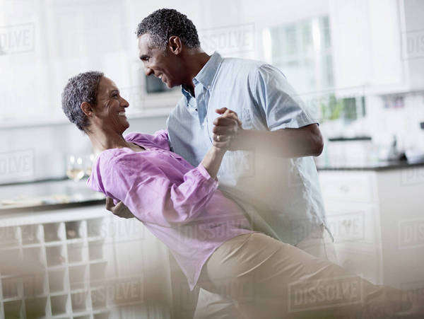 An affectionate mature African American couple, with their arms around each other dancing. Royalty-free stock photo