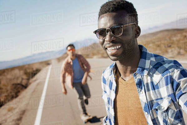 Two men on a tarmac road in open country.  Royalty-free stock photo