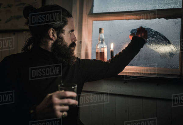 A man sitting alone in a room with a bottle of whisky and a glass, wiping condensation off the window to see outside. A lit candle. Royalty-free stock photo