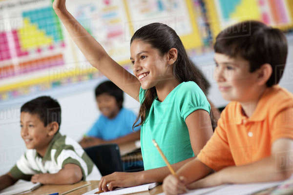 A group of young girls and boys in a classroom, classmates. A girl raising her hand.  Royalty-free stock photo