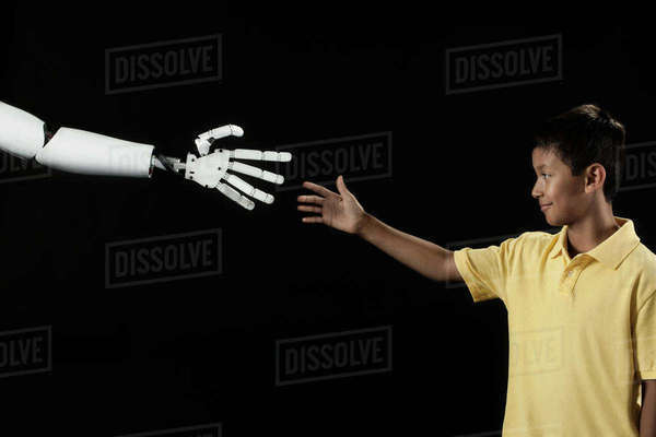 A boy reaching up to touch a robotic hand.  Royalty-free stock photo