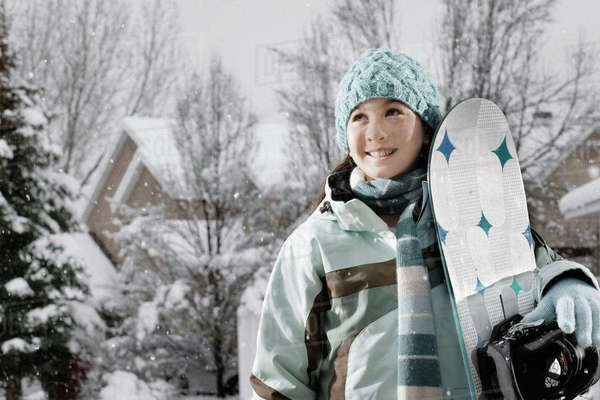 Winter snow. A girl carrying a snowboard. Royalty-free stock photo