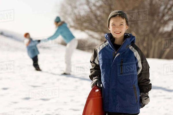 A boy holding a sledge in snow, and a mother and child behind him.  Royalty-free stock photo