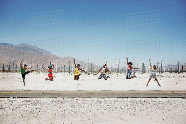 A row of six young people leaping in the air, arms outstretched in wide open space in the desert.  Royalty-free stock photo