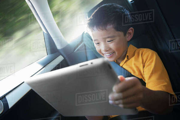 A boy travelling in the back seat of a car using a digital tablet.  Royalty-free stock photo