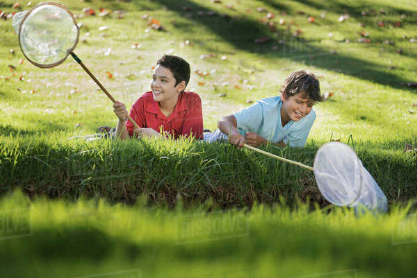 Two boys lying on the grass at the edge of a pond, using pond dipping nets.  Royalty-free stock photo