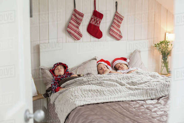 Three children in a double bed, with Christmas stockings hanging on the wall above their heads.  Royalty-free stock photo