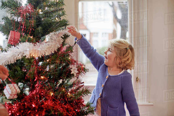 A young girl decorating a Christmas Tree at home.  Royalty-free stock photo