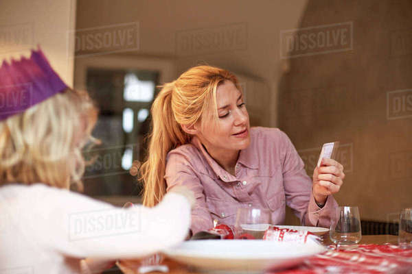 A woman and a child seated at a kitchen table sharing a cracker joke.  Royalty-free stock photo