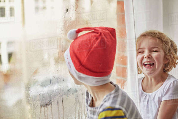 Christmas morning in a family home. A boy in a Santa hat looking out of a bedroom window and his sister laughing beside him.   Royalty-free stock photo