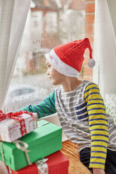 Christmas morning in a family home. A boy in a Santa hat looking out of a bedroom window.  Royalty-free stock photo