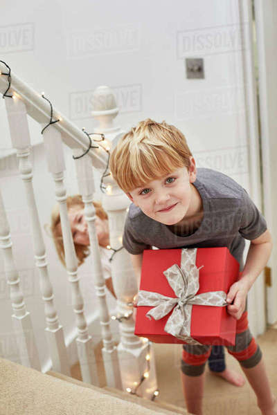 Christmas morning in a family home. Two children on the stairs carrying presents.  Royalty-free stock photo